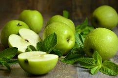 Groene appelen met muntbladeren stock afbeeldingen