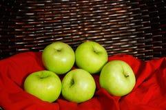 Groene appelen op rode stof met bruine mand op achtergrond Stock Afbeelding