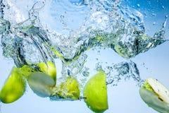 Groene appelen. Vruchten daling diep onder water met plons Stock Foto