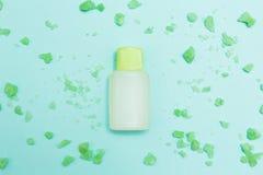 Groene bad zoute en aromatische olie op een blauwe achtergrond stock foto's