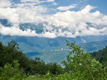 Groene berghelling met kronkelige weg die in de vallei daalt stock afbeeldingen