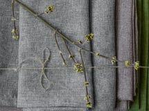 Groene bladeren die op de gevouwen grijze stoffen hoogste mening leggen stock fotografie
