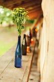 Groene bloemen in blauwe fles op aard Royalty-vrije Stock Afbeelding