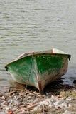Groene boot bij waterenrand stock foto