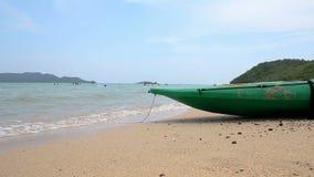 Groene boot op het zandstrand met aard overzees omringend geluid stock video
