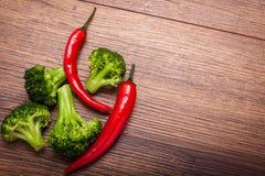 Groene broccoli, rode Spaanse peper op een houten oppervlakte Hoogste mening met exemplaarruimte voor tekst Stock Foto