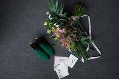 Groene bruids schoenen, rijk groen huwelijksboeket met roze linten en huwelijk het vleiende liggen op een grijze vloer Stock Fotografie