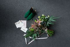Groene bruids schoenen, rijk groen huwelijksboeket met roze linten en huwelijk het vleiende liggen op een grijze vloer Royalty-vrije Stock Foto