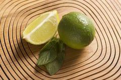 Groene citroen en munt op houten achtergrond stock foto