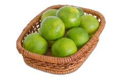 Groene citroenen in een rieten mand Stock Afbeeldingen