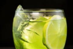 Groene cocktail met jenever, bittere citroen, basilicum en citroen stock foto