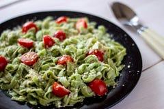 Groene deegwaren met tomaten en parmezaanse kaaskaas stock afbeeldingen
