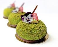 Groene desserts met aardbeien en eetbare bloemen op gouden onderleggers voor glazen stock foto's