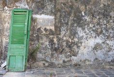 Groene deur die tegen muur leunen royalty-vrije stock afbeelding