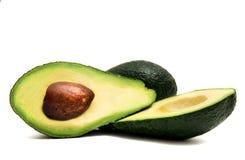 Groene die avocado in de helft wordt gesneden die op een witte achtergrond liggen stock afbeeldingen