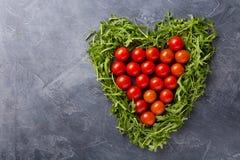Groene die bladeren van arugula in de vorm van hart, tomaten binnen op donkere achtergrond wordt opgemaakt royalty-vrije stock foto's