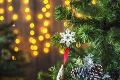 Groene die Kerstboom met Kerstmisspeelgoed wordt verfraaid en een slinger met gele lichten Stock Fotografie