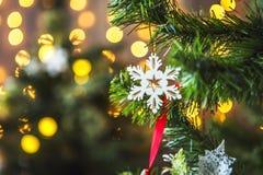 Groene die Kerstboom met Kerstmisspeelgoed wordt verfraaid en een slinger met gele lichten Royalty-vrije Stock Fotografie