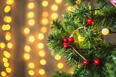 Groene die Kerstboom met Kerstmisspeelgoed wordt verfraaid en een slinger met gele lichten Stock Foto's