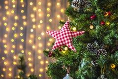 Groene die Kerstboom met Kerstmisspeelgoed wordt verfraaid en een slinger met gele lichten Stock Foto