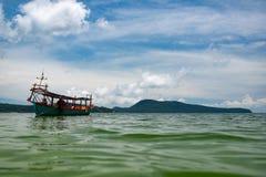 Groene die Longtail-boot in Saracene Baai in Koh Ron Samloem, Kambodja wordt vastgelegd stock afbeelding