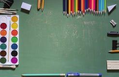 Groene die schoolraad met een notitieboekje door een verscheidenheid van bureaus wordt omringd stock afbeeldingen
