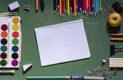 Groene die schoolraad met een notitieboekje door een verscheidenheid van bureaus wordt omringd royalty-vrije stock afbeeldingen