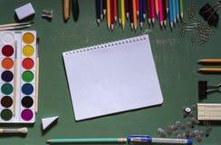 Groene die schoolraad met een notitieboekje door een verscheidenheid van bureaus wordt omringd stock foto