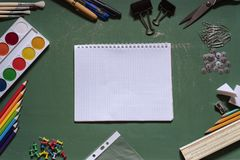Groene die schoolraad met een notitieboekje door een verscheidenheid van bureaus wordt omringd royalty-vrije stock foto's