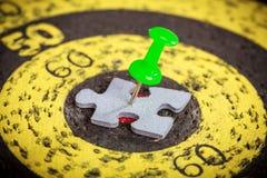 Groene die speld aan de puzzelstuk van de mensenvorm wordt gehouden op oude doelraad Stock Foto