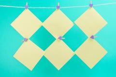 Groene die stickers op drooglijn met wasknijpers op blauwe achtergrond worden ge?soleerd royalty-vrije stock foto