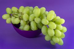 Groene druiven in kom op proton purpere achtergrond royalty-vrije stock afbeelding
