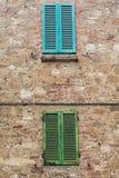 Groene en Blauwe blinden op steenmuur Stock Afbeeldingen