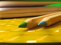 Groene en blauwe potloden op gele lijst Stock Afbeelding