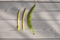 Groene en gele bonen op een grijze houten lijst stock afbeeldingen