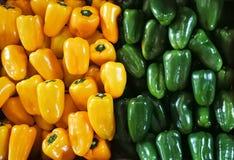 Groene en gele groene paprika's op een teller in de supermarkt Kleurrijke zoete groene paprika's in a Stock Foto