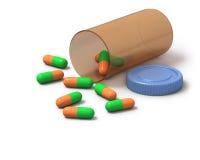 Groene en oranje capsules op witte achtergrond Stock Afbeelding