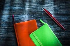 Groene en oranje notitieboekjes op houten raad royalty-vrije stock fotografie