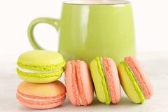 Groene en roze kleurrijke makarons met groene mok Royalty-vrije Stock Foto's