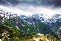 Groene en sneeuwbergen met donkere hierboven onweerswolken Stock Afbeeldingen