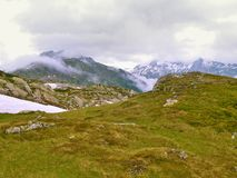 Groene en sneeuwweiden van hoge Alpiene bergen Stock Fotografie
