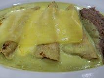 groene enchiladas met gesmolten kaas en refried bonen, typisch Mexicaans voedsel royalty-vrije stock afbeeldingen