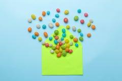 Groene envelop en multi-colored suikergoed op een heldere in lichtblauwe achtergrond Hoogste mening royalty-vrije stock foto's