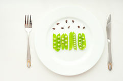 Groene erwten in bonen met cedernoten op witte plaat Royalty-vrije Stock Foto