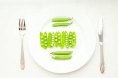 Groene erwten in bonen op witte plaat Stock Afbeeldingen
