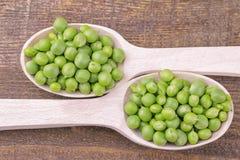 groene erwten in houten lepelsclose-up op een bruine houten lijst Hoogste mening royalty-vrije stock afbeelding