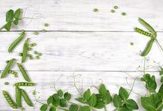 Groene erwten met bladeren op de witte houten mening van de lijstbovenkant Stock Afbeelding