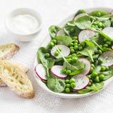 Groene erwten, radijs en babyspinaziesalade op ceramische plaat op een lichte achtergrond Royalty-vrije Stock Afbeeldingen