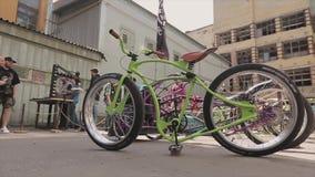Groene fiets met verschillende wielentribune op straat overeenkomstig andere tentoonstelling Zonnige de zomerdag stock video