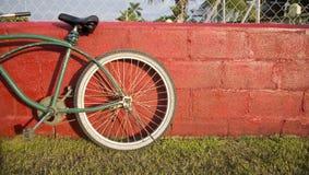 Groene fiets rode muur Stock Afbeeldingen